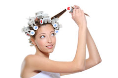 Curling of hair by the young beautiful woman Royalty Free Stock Image