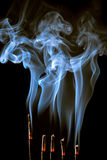 Curling incense smoke. Incense burning with beautiful smoke fumes and wisps royalty free stock photo