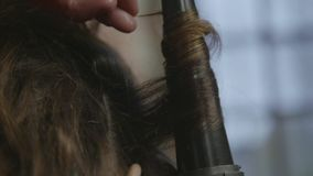 Curling Iron in Use. Close up of stylist`s hand using curling iron for hair curls.Wrap curlinglong brunette hair in a beauty salon stock video