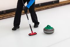 Curling - player with broom sweeping the ice before stone Stock Photography
