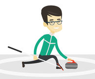 Curling player playing curling on curling rink. Royalty Free Stock Image