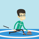 Curling player playing curling on curling rink. Royalty Free Stock Photo