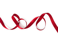 Curling Red Ribbon. Red satin ribbon, curling over white background Royalty Free Stock Image