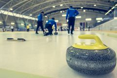 Curling stone on a game sheet. Indoor sport on ice Royalty Free Stock Photography