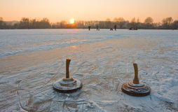 Curling stones. Two curling stones on a frozen lake at sunset Stock Photos