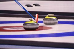 Curling Stones. And a sweeper. This game was invented in Scotland and has seen a surge in popularity since the 1998 Olympic games Stock Photography