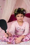 Curls. Adorable girls in her pajamas and colorful curlers looking at herself in the mirror royalty free stock photo
