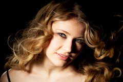 Curls. Young woman presents her golden locks Royalty Free Stock Photos