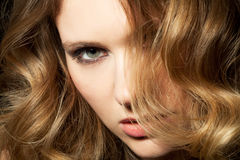 Curls. Young woman presents her golden locks Royalty Free Stock Photo