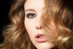 Curls. Young woman presents her golden locks Royalty Free Stock Images