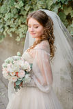 Curls cover shoulders of pretty bride stock images