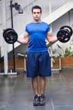 Curls with Dumbbell Weights. Male athelete / weightlifter, looking straight into camera, doing curls with dumbbell weights in his hands Stock Photos