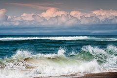 Curls of Waves and Curls of Clouds. Big Waves Breaking On The Shore stock photo