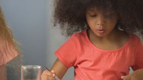 Curly African American girl painting with watercolors at kindergarten, hobby. Stock footage stock video