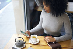 Curly African-American in a gray jacket sitting in cafe using wireless internet and phone Royalty Free Stock Photography