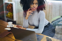 Curly African-American in a gray jacket using notebook and modern technologies to record ideas and advice Royalty Free Stock Photos