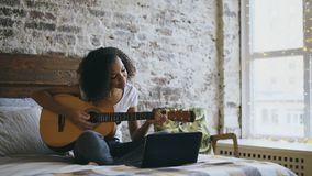 Curly african american teenager girl concentraing learning to play guitar using laptop computer sitting on bed at home. Curly african american teenager girl Stock Image