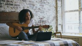 Curly african american teenager girl concentraing learning to play guitar using laptop computer sitting on bed at home stock video footage