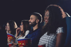 Curly african girl toothy smiling and watching film in cinema. Side view of positive company of international people watching interested movie. Curly african Stock Image