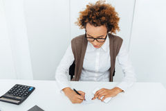 Curly african young woman accountant sitting and writing in office Royalty Free Stock Photography