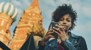 Curly afro girl with smartphone near Cathedral royalty free stock photography