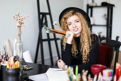Curly Artist Smiling and Holding Pencil. Romantic blonde long hair curly feemale artist in black hat sitting and smiling behind the table with color pencil, she royalty free stock photography