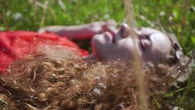 Curly attractive girl lies on the green grass. Young pretty woman closed her eyes. Cheerful lady in a red t-shirt. Summer vacation concept stock video
