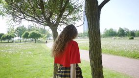 Curly attractive girl is played around the trees. Young pretty woman whirls and flirts in nature. Female in a red T stock video footage