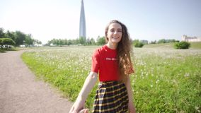 Curly attractive girl pulls the guy's hand. Young pretty woman is walking on the field. Cheerful lady in a red t-shirt stock footage