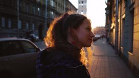 Curly attractive girl smiles and looks cute. Young pretty woman in european city at sunset background. Girl in a blue. Jacket Close up. The concept of an stock video footage