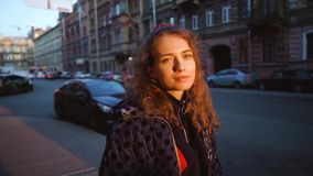 Curly attractive girl smiles and looks cute. Young pretty woman in european city at sunset background. Girl in a blue stock footage