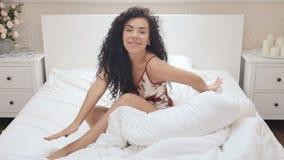Beautiful brunette basks in bed stock video footage