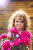 Curly baby with flowers in her hand. Toning photo.   Stock Photo