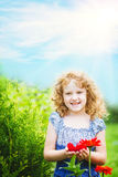 Curly baby with flowers in her hand. Stock Images