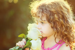 Curly baby with flowers in her hand. Toning photo. Instagram filter. stock image
