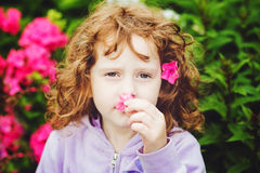 Curly baby with flowers in her hand. Toning photo. Instagram fil Royalty Free Stock Photography