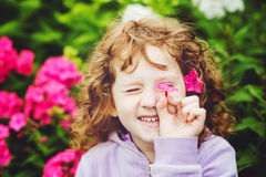 Curly baby with flowers in her hand. Toning photo. Royalty Free Stock Photography
