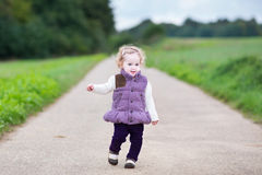 Curly baby girl on country road on cold day Stock Photos