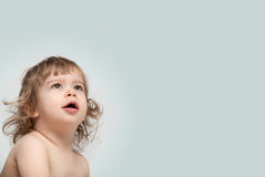 Curly baby looking up amazed Royalty Free Stock Photography