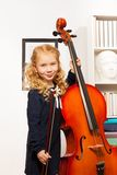 Curly beautiful girl with fiddlestick, violoncello. Curly beautiful girl holding the fiddlestick to play violoncello indoors Royalty Free Stock Images
