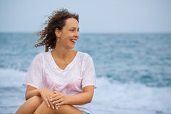 Curly beautiful woman sitting near sea in evening Royalty Free Stock Images
