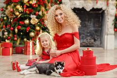 Curly beautiful young blond woman and a daughter in a red dress royalty free stock images