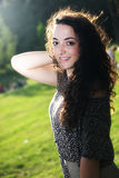 Curly, beautiful young girl with slight smile in the green park stock image