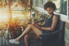 Curly black girl with phone on bench Royalty Free Stock Photo