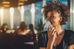 Curly black girl using her phone as voice recorder. Young curly black female in luxury office space recording audio message via her smartphone, afro american Royalty Free Stock Images