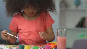 Curly black-haired girl painting with watercolors at art school, art hobby. Stock footage stock video footage
