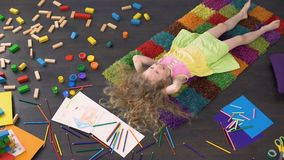 Curly blond child lying on the carpet dreaming and laughing, happy childhood. Stock footage stock video
