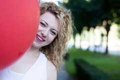 Curly blond girl with big red ballon Stock Image
