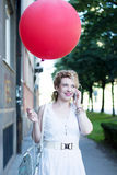 Curly blond girl with big red ballon on the phone Stock Images