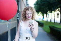 Curly blond girl with big red ballon on the phone Royalty Free Stock Photos